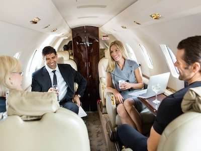 Business travelers inside a business jet as part of the business aviation industry by high tech finishing.